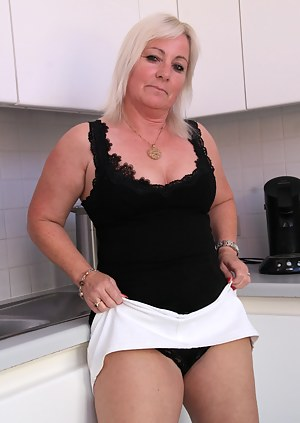 Blonde housewife playing with her pussy in the kitchen