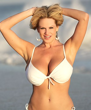 Kelly strolls on the beach in a white bikini and gets wet.
