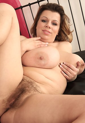 Busty mature Vanda is having some trouble keeping her huge tits in her little silky dress. Will you help her out of it so she can finger her hairy twat?