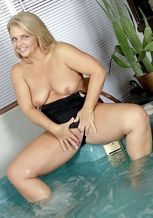 Horny 50 year old Kelly fingers her bald pussy in the hot tub