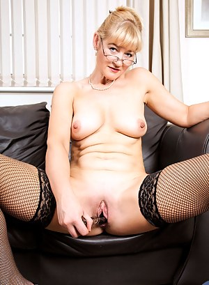 Classy businesswoman loosens up on the sofa and pleasures her seasoned milf pussy