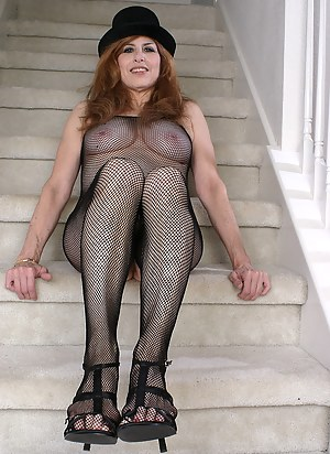 Redheaded grandma in a fishnet body stocking plays with her feet