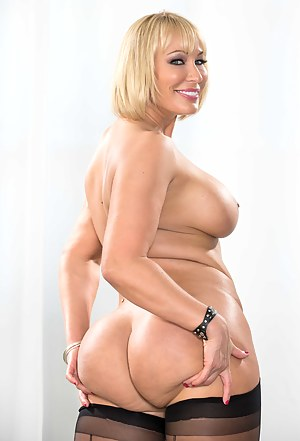 Blonde chubby MILF is looking so sexy wearing black stockings. She is touching her giant melons while having ass fucking session with her man.