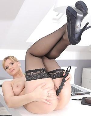 37 year old Charlotta Rose spreads her long legs on her office desk